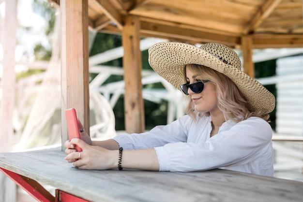 Ładna pani trzyma komórkę i robi selfie w pobliżu drewnianej altanki w upalny letni dzień