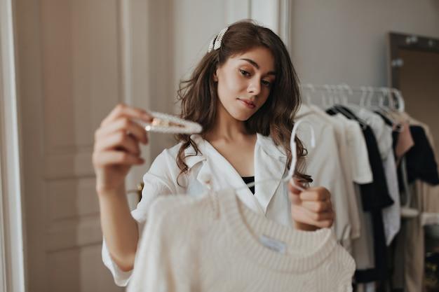 Ładna pani trzymająca białą szpilkę do włosów i beżowy sweter