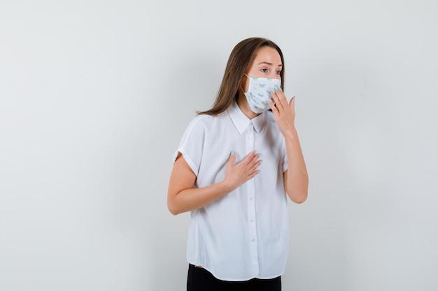 Ładna pani trzymająca rękę na klatce piersiowej i w pobliżu maski