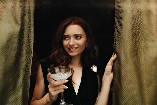 Ładna pani w aksamitnej sukience trzyma kieliszek do martini