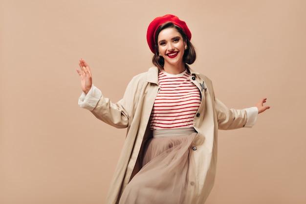 Ładna pani w beżowym stroju taniec na na białym tle. śliczna stylowa kobieta z czerwonymi ustami w jasnym berecie, długiej spódnicy i płaszczu uśmiecha się.