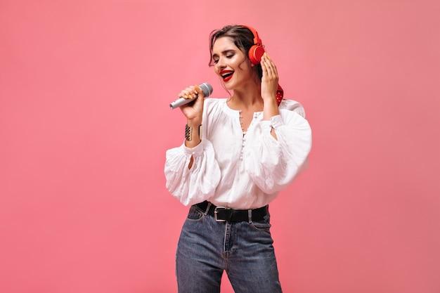 Ładna pani w białej bluzce śpiewa i słucha muzyki w słuchawkach. piękna młoda kobieta w stylowy strój pozowanie na różowym tle.