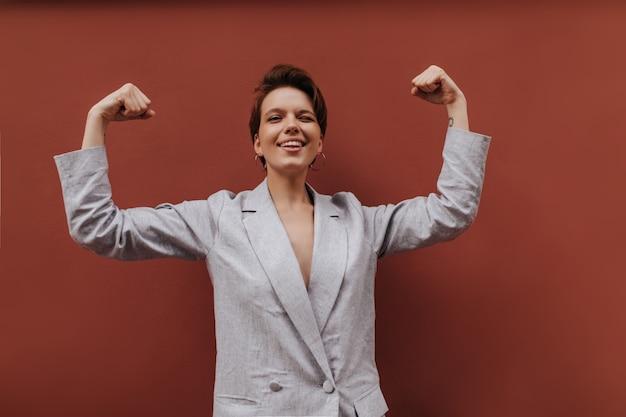 Ładna pani w garniturze pokazując bicepsy na brązowym tle. krótkowłosa kobieta w szarej stylowej kurtce demonstruje moc na odosobnieniu