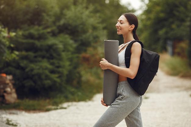 Ładna pani w parku. brunetka przygotowuje się do jogi. dziewczyna w stroju sportowym.