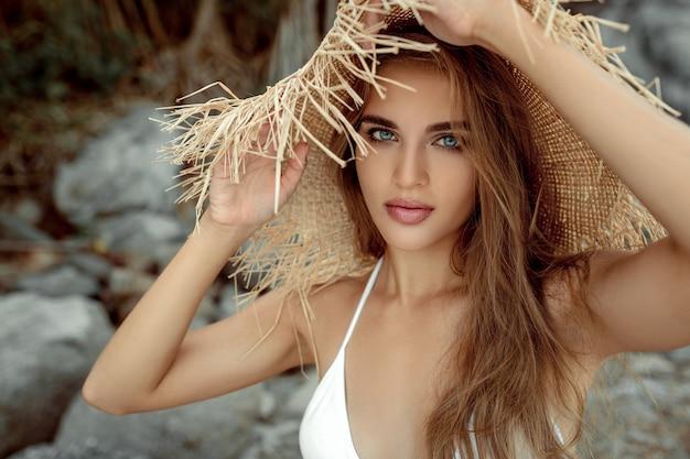 Ładna pani w słomkowym kapeluszu i stroju kąpielowym