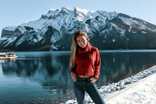 Ładna pani z białym uśmiechem stojąc na plaży w pobliżu jeziora. góry pokryte śniegiem. ubrana w czerwony sweter z dzianiny i niebieskie dżinsy. długa blond fryzura, bez makijażu.