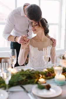Ładna panna młoda i pan młody w pobliżu weselnego stołu z tortem ślubnym, niebieskie świece i dekoracje sosnowe