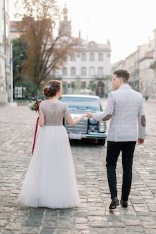 Ładna panna młoda i przystojny pan młody spaceru w starym centrum miasta, stojący przed czarnym samochodem retro