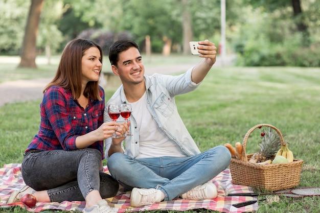 Ładna para biorąc selfie trzymając kieliszki do wina
