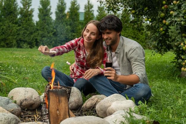 Ładna para biwakuje z piankami przy ognisku szczęśliwa młoda para relaksuje się na podwórku