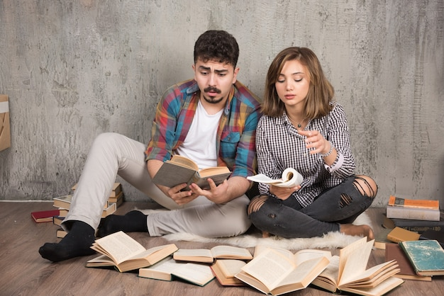 Ładna para czyta książki siedząc na podłodze