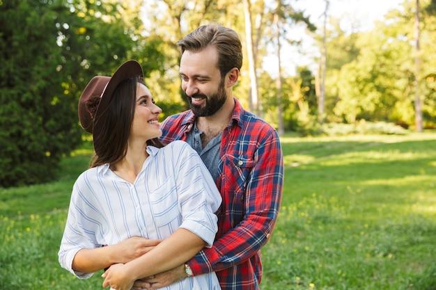Ładna para mężczyzna i kobieta ubrani w codzienny strój przytulający się razem podczas spaceru po zielonym parku