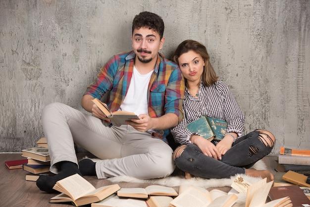 Ładna para siedzi na podłodze z dużą ilością książek