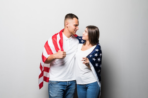 Ładna para trzyma flagę usa w dłoniach, zakrywają się, patrząc na siebie na białym tle