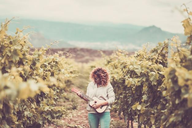 Ładna piękna kaukaska kobieta chodzi samotnie po winnicy zielone tło śpiewa na gitarze akustycznej na ukulele