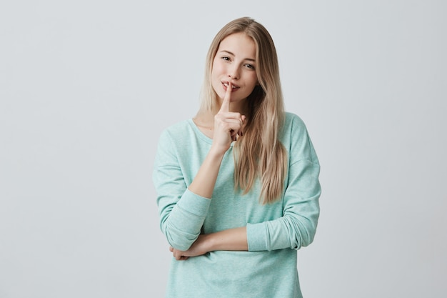 Ładna piękna kobieta trzyma palec na uśmiechniętych ustach, wykazuje znak ciszy, prosi o zachowanie spisku lub ciszy, stara się ukryć sekret