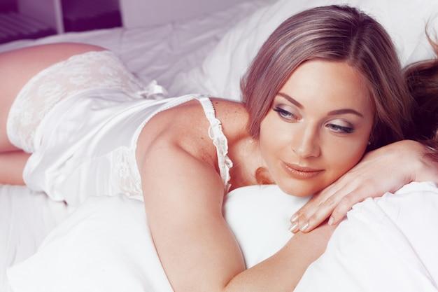 Ładna piękna panna młoda kobieta o seksownym ciele leżącym w bieliźnie na białym łóżku