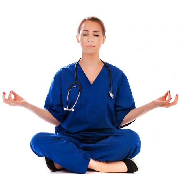 Ładna pielęgniarka robi medytaci odizolowywającej na bielu