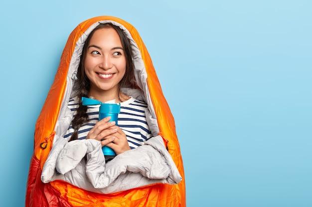 Ładna podróżniczka nosi sweter w paski, owinięta w śpiwór, trzyma termos z gorącym napojem, lubi kempingowy styl życia, ma letnie wakacje i przygodę, ma czarujący, zębaty uśmiech na twarzy
