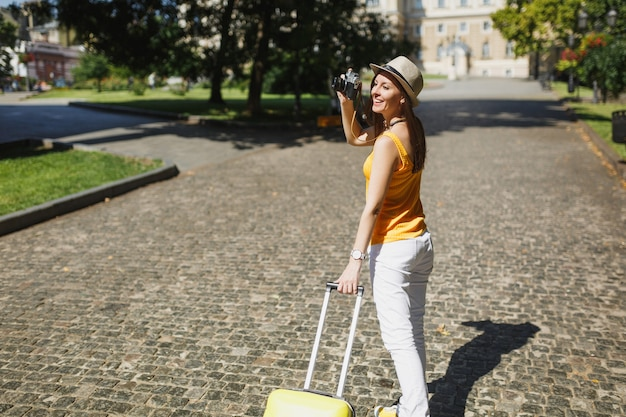 Ładna podróżniczka turystyczna kobieta w żółtych ubraniach z walizką robienia zdjęć na retro vintage aparat fotograficzny spaceru w mieście na świeżym powietrzu. dziewczyna wyjeżdża za granicę na weekendowy wypad. styl życia podróży turystycznej.