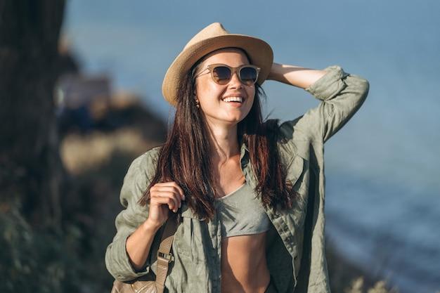 Ładna podróżniczka w kapeluszu i okularach przeciwsłonecznych z morzem w tyle.