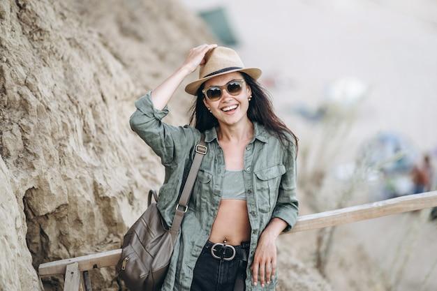 Ładna podróżniczka w kapeluszu i okularach przeciwsłonecznych ze skałami w tyle.