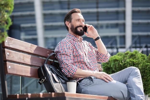 Ładna pogoda. wesoły przyjemny mężczyzna odpoczywa na ławce, ciesząc się rozmową telefoniczną