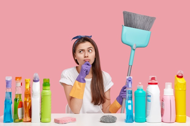 Ładna pokojówka ma zamiar, rozgląda się w zamyśleniu, ubrana w zwykły strój, trzyma miotłę, wykonuje prace domowe