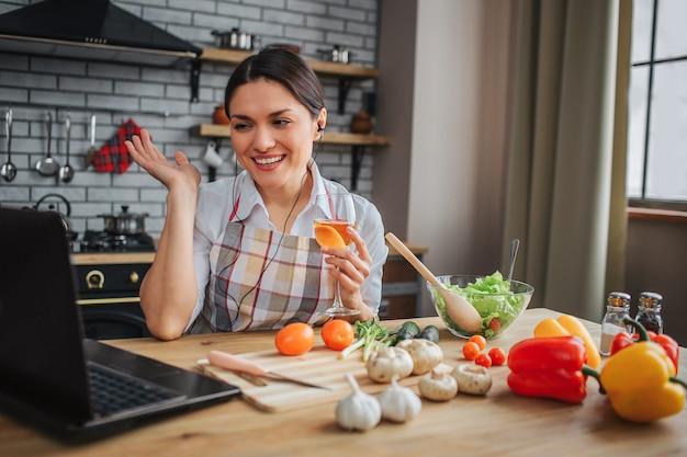 Ładna pozytywna kobieta siedzi przy stole w kichen