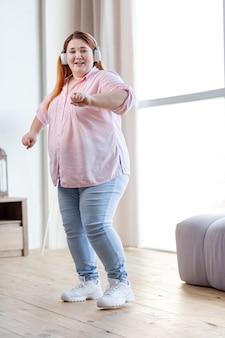 Ładna, pozytywna kobieta tańczy do swojej ulubionej piosenki podczas zabawy w domu