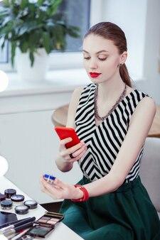 Ładna pozytywna kobieta trzymająca butelkę z kosmetykami podczas robienia zdjęcia smartfonem