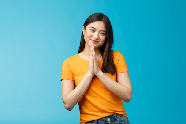 Ładna proszę dziewczyno grzecznie pytając. śliczna urocza azjatycka kobieta uśmiecha się czule, trzyma się za ręce, modli się uśmiechając się błagając o łaskę, błaga, dziękuje za pomoc stoi na niebieskim tle radosna, opiekuńcza.