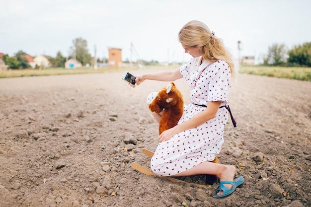 Ładna przyglądająca piękna blondynki dziewczyna robi selfie fotografii na telefonie podczas gdy jadący zabawkarskiego konia w polu.