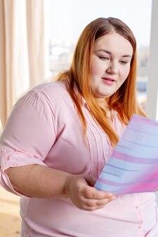 Ładna, pulchna młoda czyta magazyn o zdrowiu, jednocześnie chcąc być zdrowym