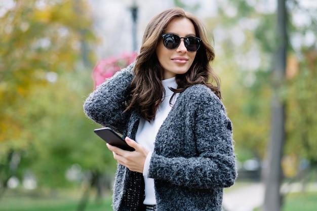 Ładna, radosna dziewczyna o krótkich, ciemnych włosach w stylowym szarym swetrze spędza weekend na świeżym powietrzu. atrakcyjna młoda kobieta z modną fryzurę idąc ulicą przez park