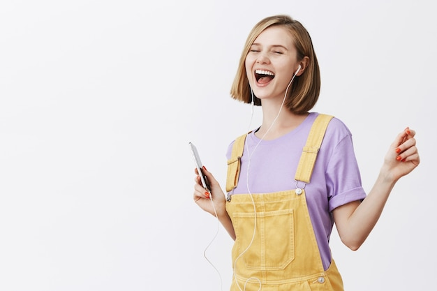Ładna, radosna kobieta tańczy beztrosko z zamkniętymi oczami, trzymając smartfon, słuchając muzyki w słuchawkach