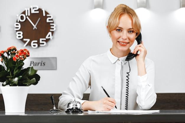 Ładna recepcjonistka w hotelu rozmawia przez telefon