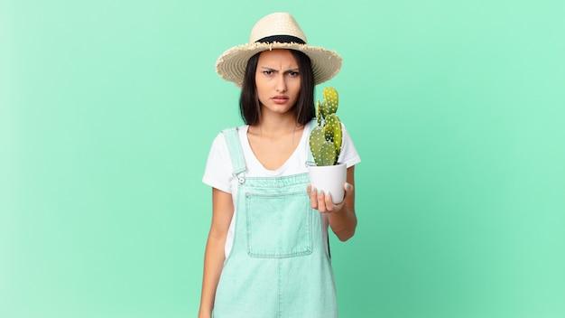 Ładna rolniczka czuje się zdezorientowana i zdezorientowana, trzymając kaktusa