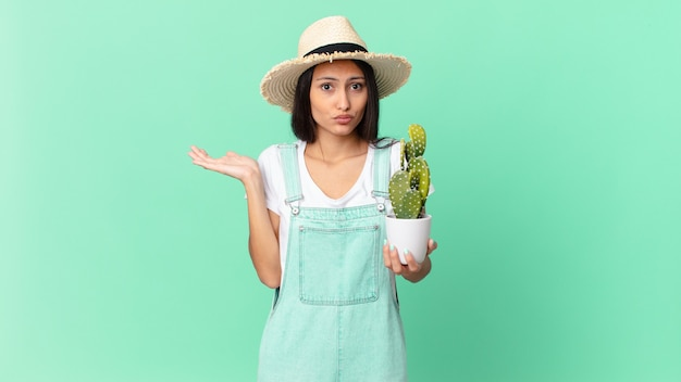Ładna rolniczka czuje się zdziwiona i zdezorientowana, wątpi i trzyma kaktusa