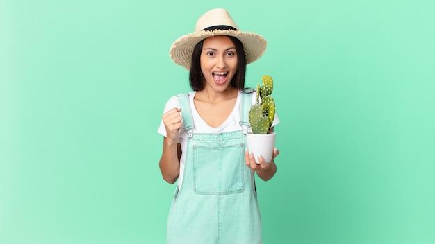 Ładna rolniczka czuje się zszokowana, śmieje się, świętuje sukces i trzyma kaktusa