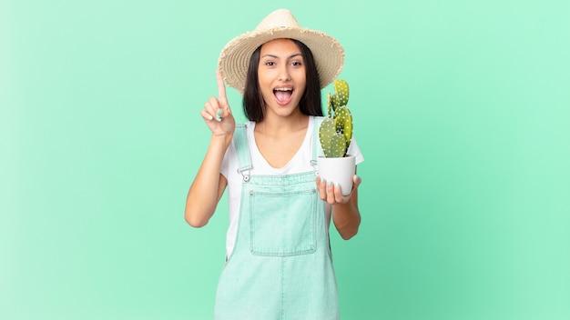 Ładna rolniczka, która czuje się jak szczęśliwy i podekscytowany geniusz po zrealizowaniu pomysłu i trzymaniu kaktusa