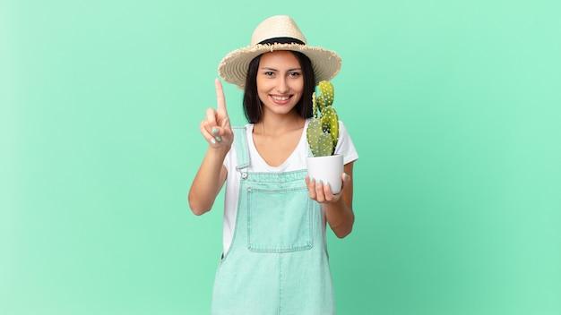 Ładna rolniczka, uśmiechnięta dumnie i pewnie, robiąca numer jeden i trzymająca kaktusa