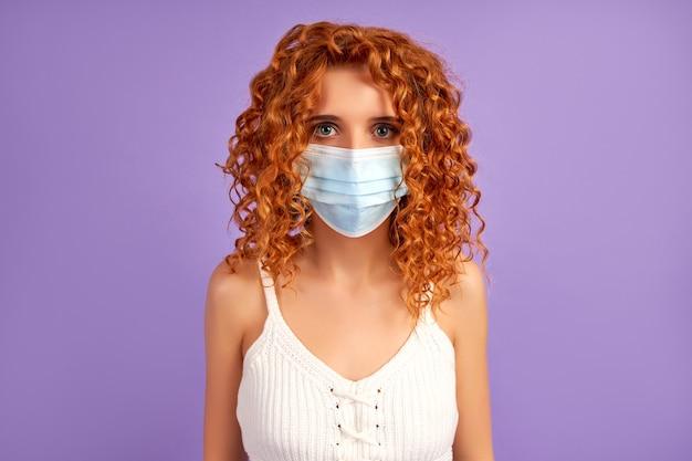 Ładna ruda dziewczyna z lokami w ochronnej masce medycznej na białym tle na fioletowej ścianie.