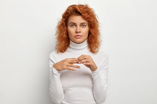 Ładna ruda kobieta drapie się po palcach, trzyma ręce razem, poważnie patrzy w kamerę