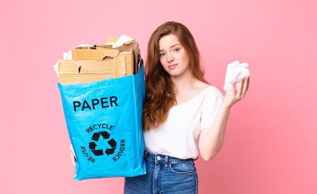 Ładna ruda kobieta trzymająca papierową torbę z recyklingu