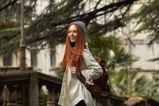 Ładna ruda kobieta w płaszczu w poszukiwaniu pięknego historycznego miejsca patrząc na atrakcje piękna kobieta spędza czas na świeżym powietrzu spacerując samotnie stojąc na historycznym balkonie