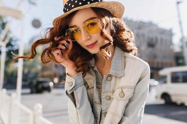 Ładna rudowłosa dziewczyna figlarnie dotykając jej żółte okulary przeciwsłoneczne. zewnątrz zdjęcie uroczej rudowłosej kobiety w kapeluszu spędzania czasu w mieście.