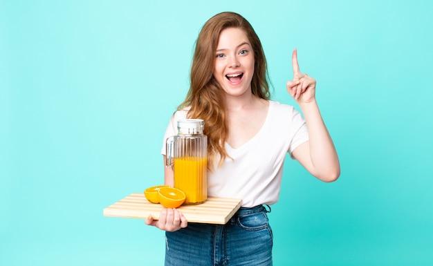 Ładna rudowłosa kobieta czuje się jak szczęśliwy i podekscytowany geniusz po zrealizowaniu pomysłu i trzymaniu soku pomarańczowego