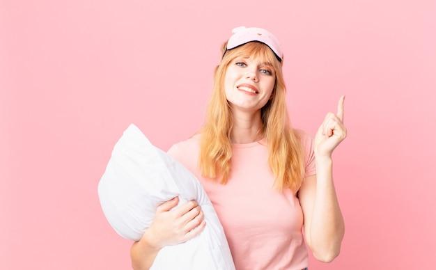 Ładna rudowłosa kobieta czuje się jak szczęśliwy i podekscytowany geniusz po zrealizowaniu pomysłu. w piżamie i trzymając poduszkę