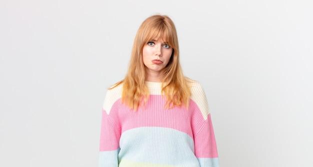 Ładna rudowłosa kobieta czuje się smutna i jęczy z nieszczęśliwym spojrzeniem i płaczem